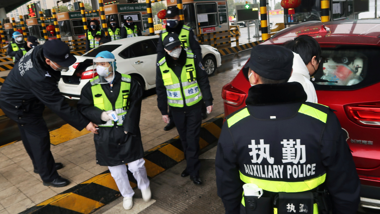 Police officers wearing masks check the boot of a car for smuggled wild animals following the outbreak of a new coronavirus, at an expressway toll station on the eve of the Chinese Lunar New Year celebrations, in Xianning, a city bordering Wuhan to the north, Hubei province, China January 24, 2020. REUTERS/Martin Pollard (China)
