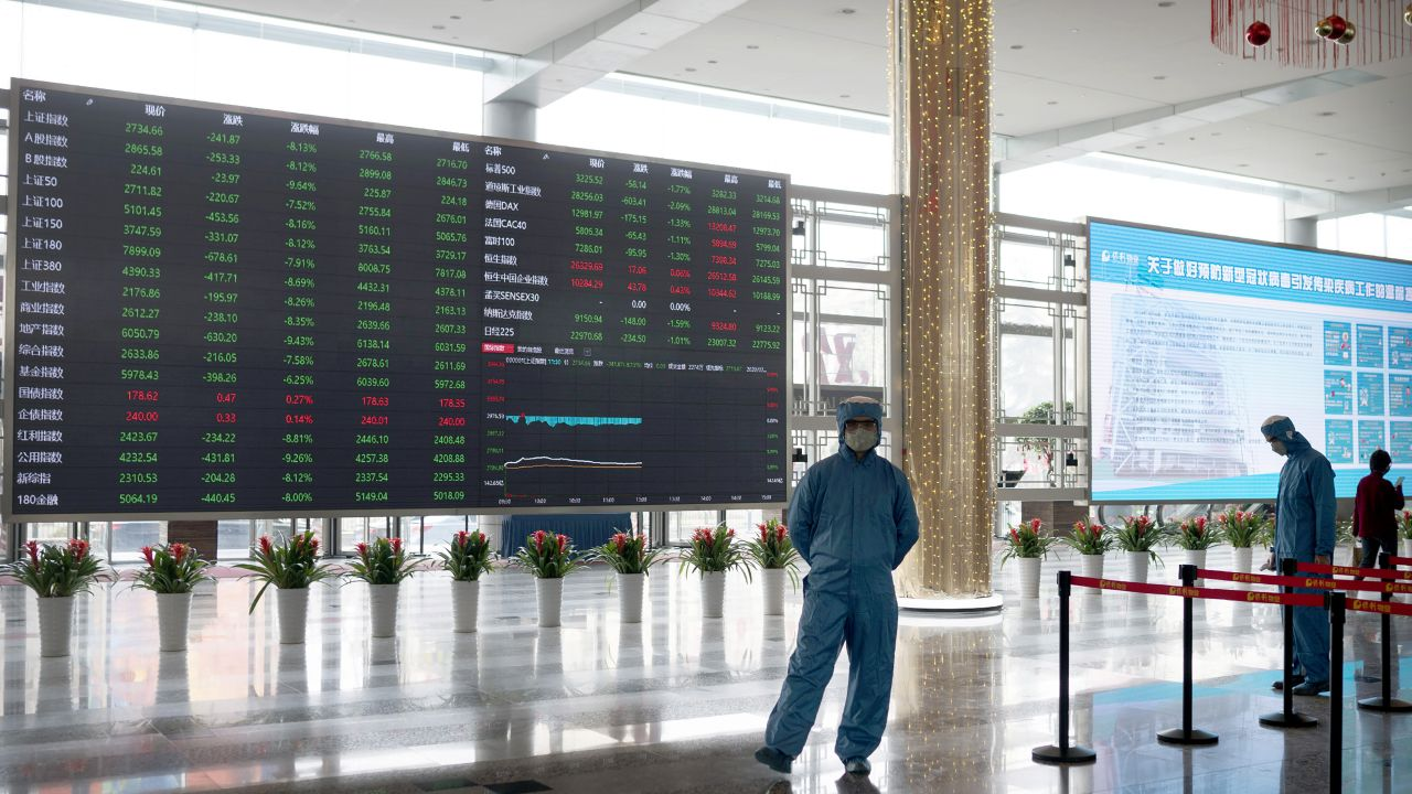 Workers wearing protective suits stand near an electronic display board in the lobby of the Shanghai Stock Exchange building in Shanghai, Monday, Feb. 3, 2020. The Shanghai Composite index tumbled 8.7% Monday then rebounded slightly as Chinese regulators moved to stabilize markets reopening from a prolonged national holiday despite a rising death toll from a new virus that has spread to more than 20 countries. (AP Photo)