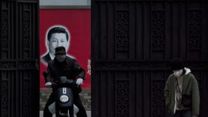People wearing masks are seen in front of a portrait of Chinese President Xi Jinping on a street as the country is hit by an outbreak of the novel coronavirus, in Shanghai, China, February 10, 2020. REUTERS/Aly Song (China)