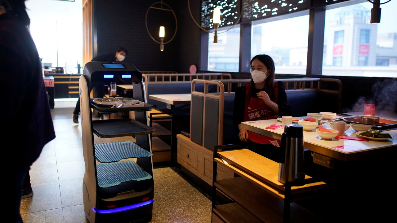 A robot transports food to serve to diners at a restaurant, following an outbreak of the novel coronavirus disease (COVID-19), in Shanghai, China March 19, 2020. REUTERS/Aly Song (China)