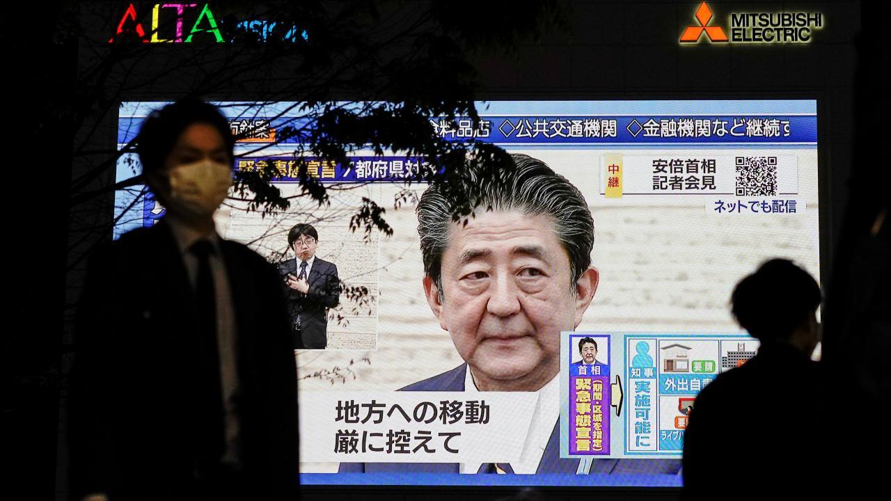 安倍首相の緊急事態宣言発令映像が街中で(写真:ロイター/アフロ)