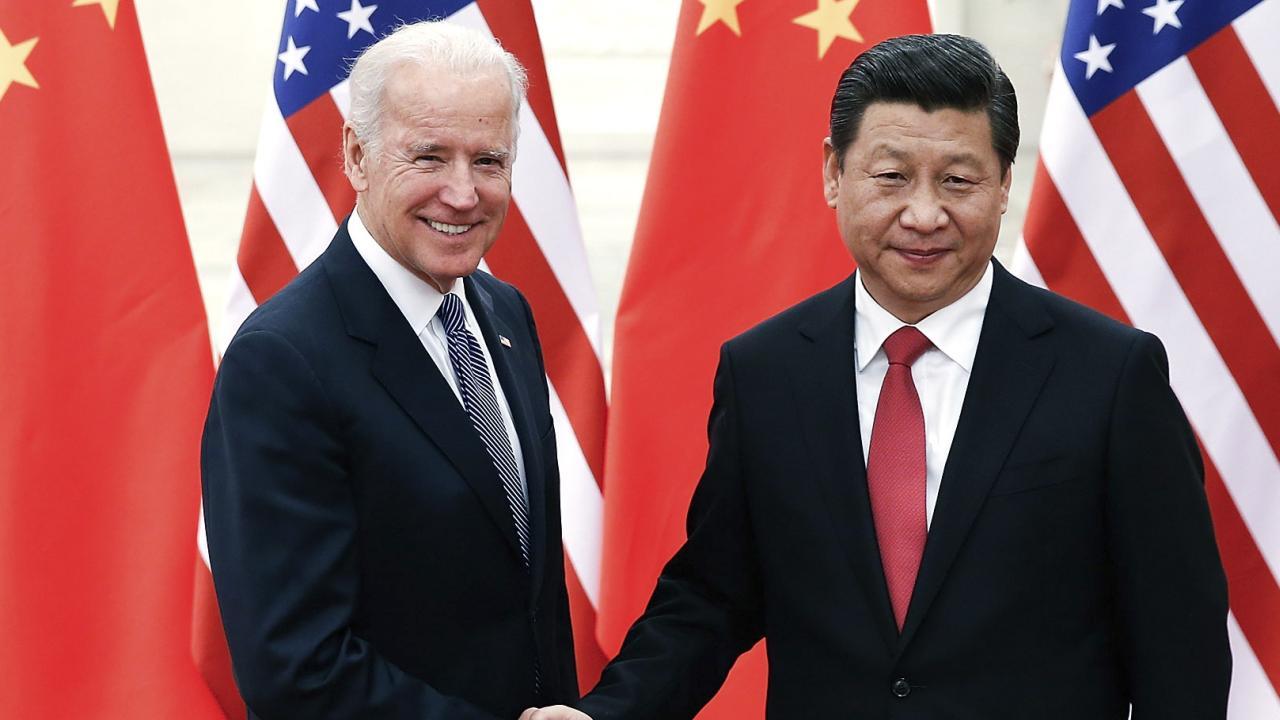 2013年12月、訪中したバイデン副大統領と握手する習近平国家主席(写真:代表撮影/AP/アフロ)