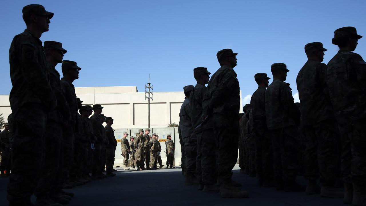 U.S. service members stand during a ceremony on the thirteenth anniversary of the 9/11 terrorist attacks in front of the World Trade Center Memorial, at Bagram Airfield, Afghanistan Thursday, Sept. 11, 2014. (AP Photo/Massoud Hossaini)